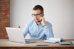 Encargado serio apuesto joven de las finanzas en los vidrios y la camisa azul que se sientan en la oficina de la compañía, mirand fotos de archivo libres de regalías