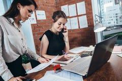 Encargado superior de sexo femenino ocupado que habla en el teléfono mientras que su ayudante que le muestra estadísticas financi fotografía de archivo