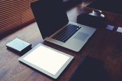 Encargado superior joven en la tabla del último ordenador portátil de la generación, taza de café, placa de la oficina espaciosa Foto de archivo libre de regalías