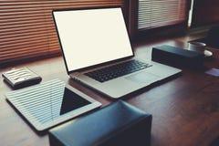 Encargado superior joven en la tabla del último ordenador portátil de la generación, taza de café, placa de la oficina espaciosa Foto de archivo