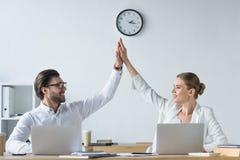 encargados acertados felices que trabajan con los ordenadores portátiles junto en la oficina y el donante foto de archivo