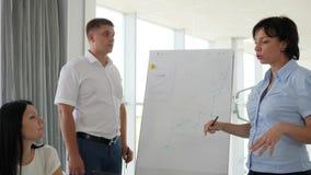 Encargados al lado del whiteboard que discuten el desarrollo de negocios en forma del diagrama metrajes