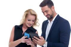 Encargados jovenes que comparan en la tableta y el smartphone aislados fotografía de archivo