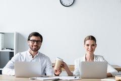 encargados que trabajan con los ordenadores portátiles junto y que pasan la taza de café de papel imagenes de archivo