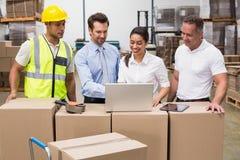 Encargados y trabajador de Warehouse que miran el ordenador portátil foto de archivo libre de regalías