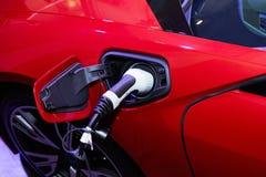 Encargando un coche eléctrico de la fuente del cable de transmisión enchufada Fotografía de archivo libre de regalías