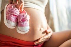 Enceinte avec des chaussures de bébé Images libres de droits