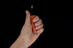 Encendedor ardiente en mano femenina imagen de archivo
