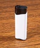 Encendedor blanco en fondo de madera. Imagen de archivo libre de regalías