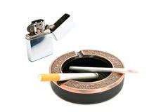 Encendedor del metal y dos cigarrillos en cenicero Imágenes de archivo libres de regalías