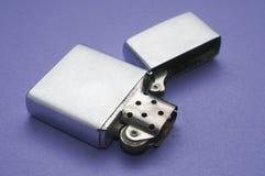 Encendedor en blanco del metal abierto en una tabla púrpura imagen de archivo