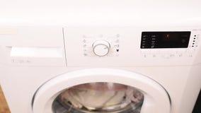 Encender la lavadora moderna blanca por la mano de la mujer almacen de video