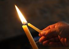 Encendiendo la vela para ruegue Fotos de archivo libres de regalías