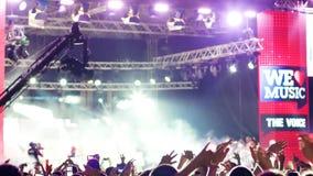 Encene a luz, multidão de povos no concerto de rocha, tiros profissionais da câmara de vídeo o concerto, é fixado ao guindaste da video estoque