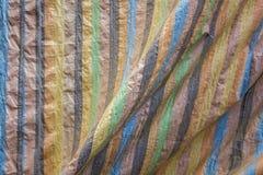 Encerado com as listras verticais coloridos e as dobras Textura da superfície áspera imagens de stock