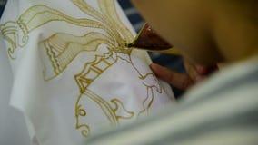 Encerar los modelos en la materia textil para el batik