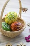Encere ovos da páscoa pintados na luz - cesta de vime marrom, decorações de madeira da flor Fotos de Stock