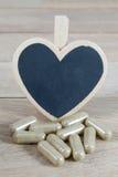 Encerre comprimidos com o quadro-negro vazio da forma do coração no backgro de madeira fotografia de stock