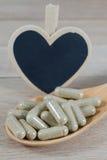 Encerre comprimidos na colher de madeira com o quadro-negro vazio da forma do coração fotos de stock