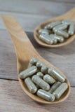 Encerre comprimidos na colher de madeira no fundo de madeira fotos de stock