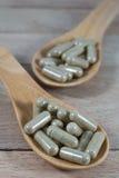 Encerre comprimidos na colher de madeira no fundo de madeira foto de stock