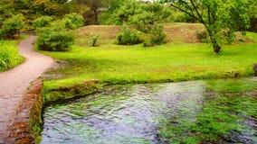 Enchanted eden garden bridge over pond in horizontal panning garden.  stock footage