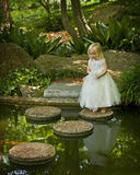 Enchanted garden. Little girl near water in garden Stock Photo