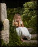 Enchanted garden. Little girl sleeping in garden Stock Image