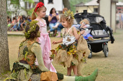 Enchanted Girl. A fantasy performer dressed and painted as a fairy captures the attention of two young girls stock photo