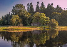 Enchanted magical place in Ireland. This little house is located in enchanted woods, and on a calm day in autumn we can beautiful reflections on the water Royalty Free Stock Photography