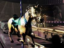 Enchanted merry-go-round. Merry-go-round with horses and cars, where a real horse is breaking his shell Stock Images