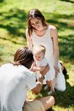 Enchanted parents are sitting on the lawn and teaching their little daughter how to make her first steps. royalty free stock image