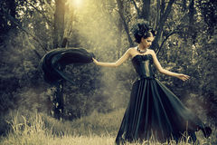 Enchanted woman. Magnificent brunette woman wearing long black dress walking in a mystic forest. The old times, the Gothic style. Fashion Royalty Free Stock Image