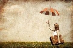 Enchanteresse rousse avec le parapluie et la valise Image libre de droits