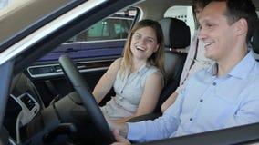 Enchantez sur la nouvelle machine, jeune famille examine le salon de voiture, banque de vidéos