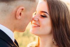 Enchanting bride looks at groom with love. While leaning to his nose royalty free stock photos