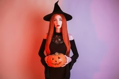 Enchanting halloween costume. Gothic woman witch with pale skin and red hair in black dress holding jack pumpkin. Girl witch with stock photo