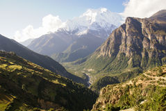 Enchanting Mountain Landscape. Beautiful Himalayan mountain landscape scene with fields and a village on the left and imposing rocky mountains on the right Royalty Free Stock Photography