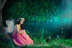 Enchanting Nymph in forest stock photo