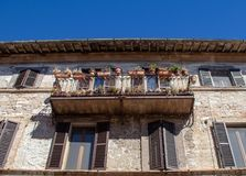 The Enchanting Streets of Asssi. A flower covered balcony along the enchanting streets of Assisi, Italy stock image