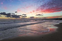 Enchanting sunset. Storm sea with high waves. Unbelievable blue, pink, orange colors of the sky are reflected on the wet sand. The mountains in haze on the stock images