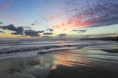 Enchanting sunset. Storm sea with high waves. Unbelievable blue, pink, orange colors of the sky are reflected on the wet sand. The mountains in haze on the stock photography