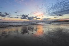 Enchanting sunset. Storm sea with high waves. Unbelievable blue, pink, orange colors of the sky are reflected on the wet sand. The mountains in haze on the stock photo