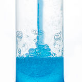 Enchendo um tubo plástico com o gel azul Fotos de Stock