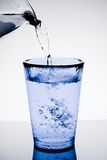 Enchendo um vidro azul com água e as bolhas puras fotos de stock royalty free