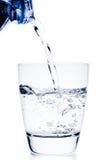 Enchendo um vidro com a garrafa do azul da calha da água Foto de Stock Royalty Free