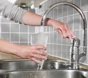 Enchendo um vidro da água Foto de Stock
