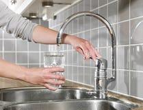 Enchendo um vidro da água Fotografia de Stock Royalty Free
