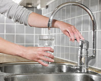 Enchendo um vidro da água Fotos de Stock Royalty Free