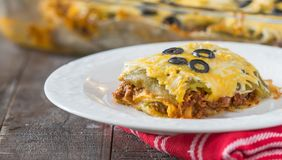 Enchilada casserole. This hot and hearty dish feeds a lot of hungry mouths. Layers of corn tortillas, meat sauce, whole green chilies and cheese is the perfect Stock Image